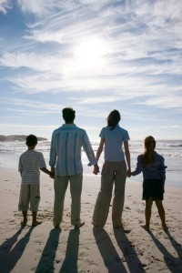 Young Couple with Two Children (8-12) Walking on the Beach --- Image by © Royalty-Free/Corbis